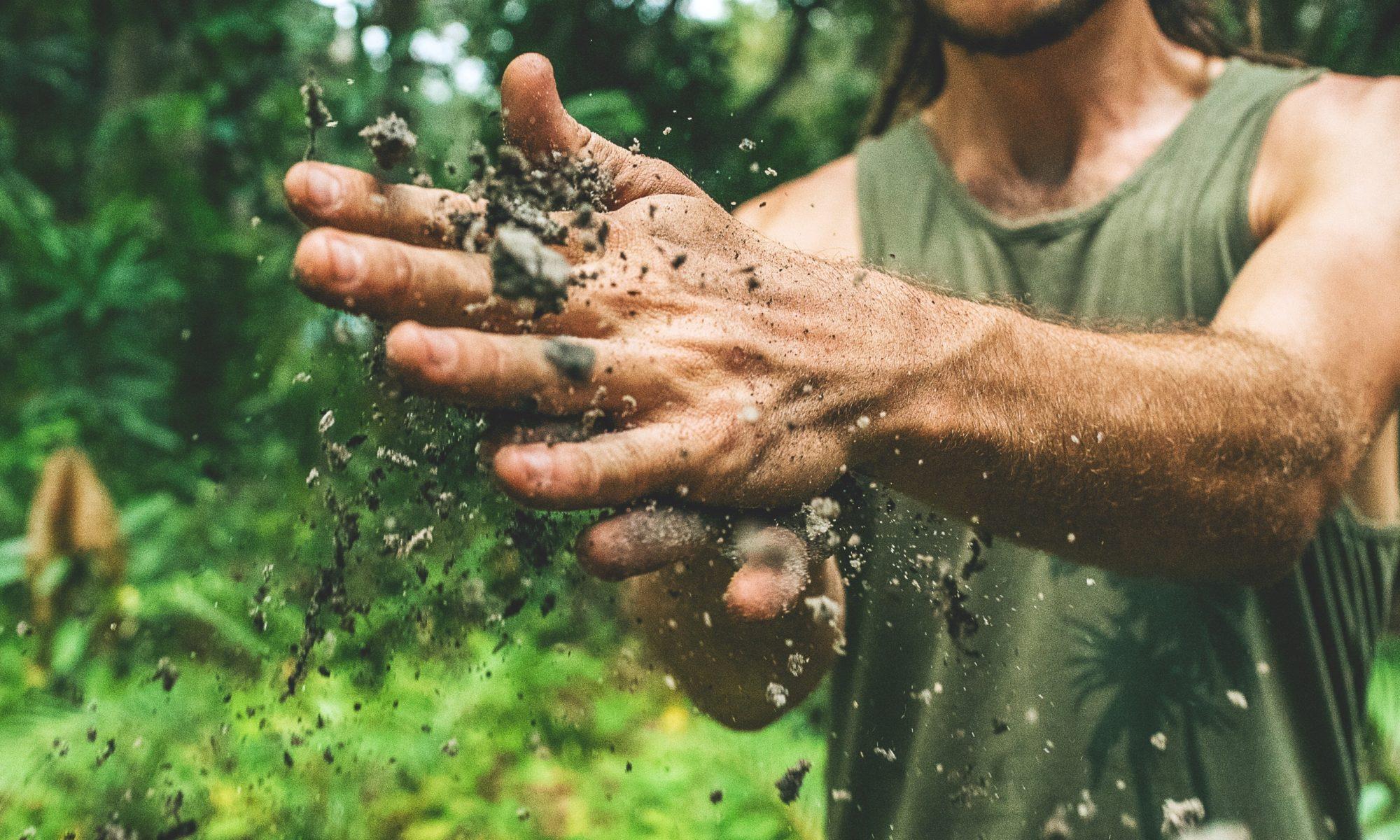Mann der Erde zwischen den Händen verreibt