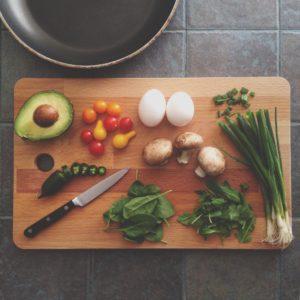 Gemüse und Eier auf einem Holz-Schneidebrett mit Messer und Pfanne