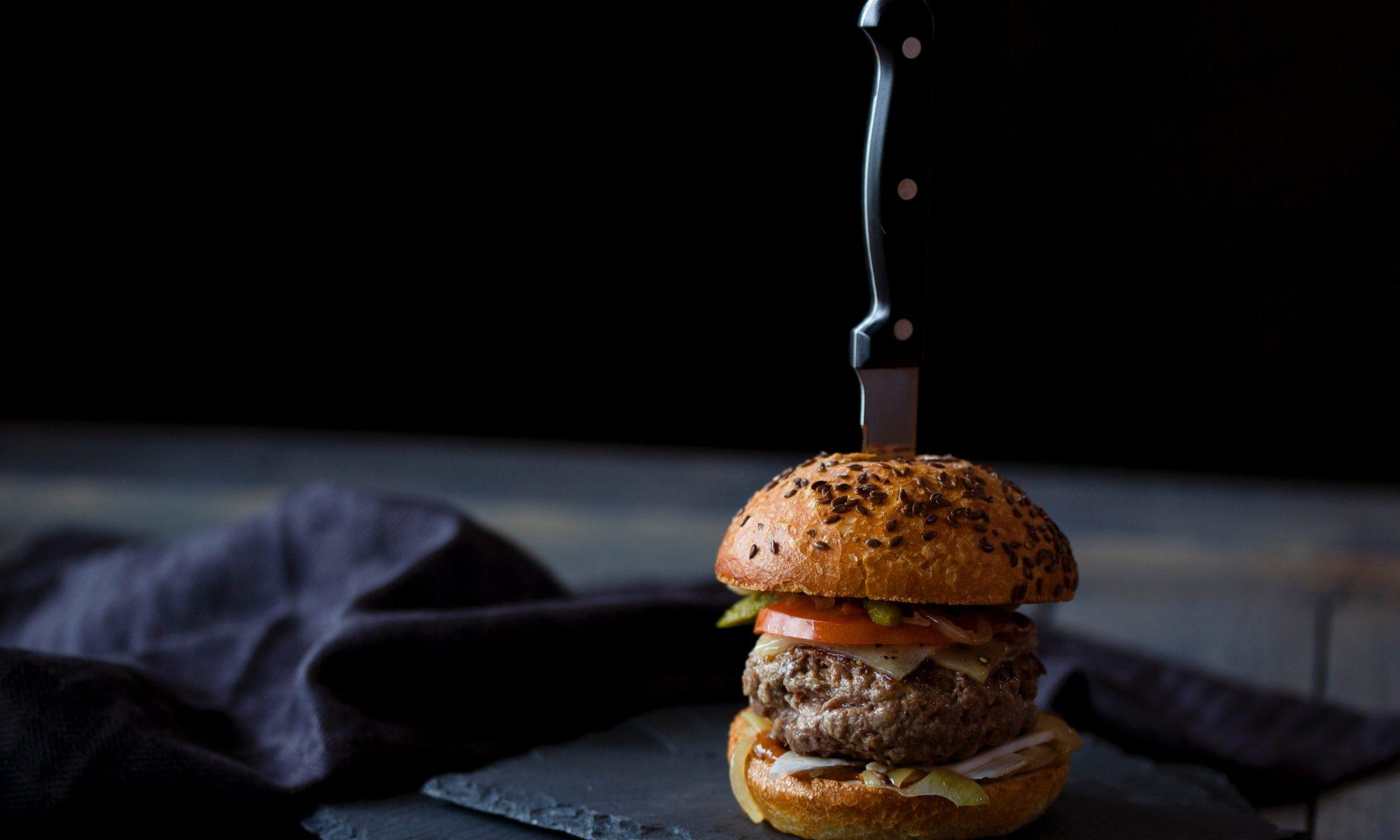 Grosser Burger in dem ein Messer steckt