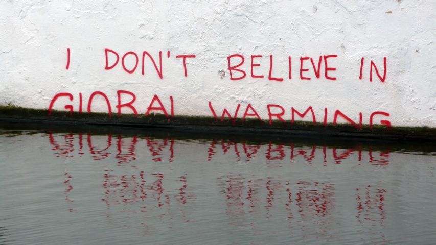 a grafitti saying I do not believe in global warming half swamped
