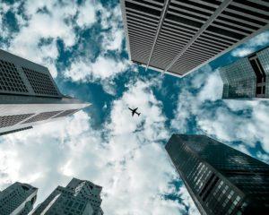 Froschperspektive eines fliegenden Flugzeugs im Wolkenhimmel zwischen Hochhäusern