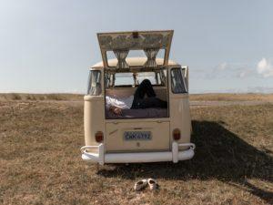 Rückseite eines VW Busses, in dem jemand auf einer Matratze liegt
