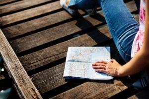Eine Landkarte, die von einer Frau auf einem Holzsteg festgehalten wird