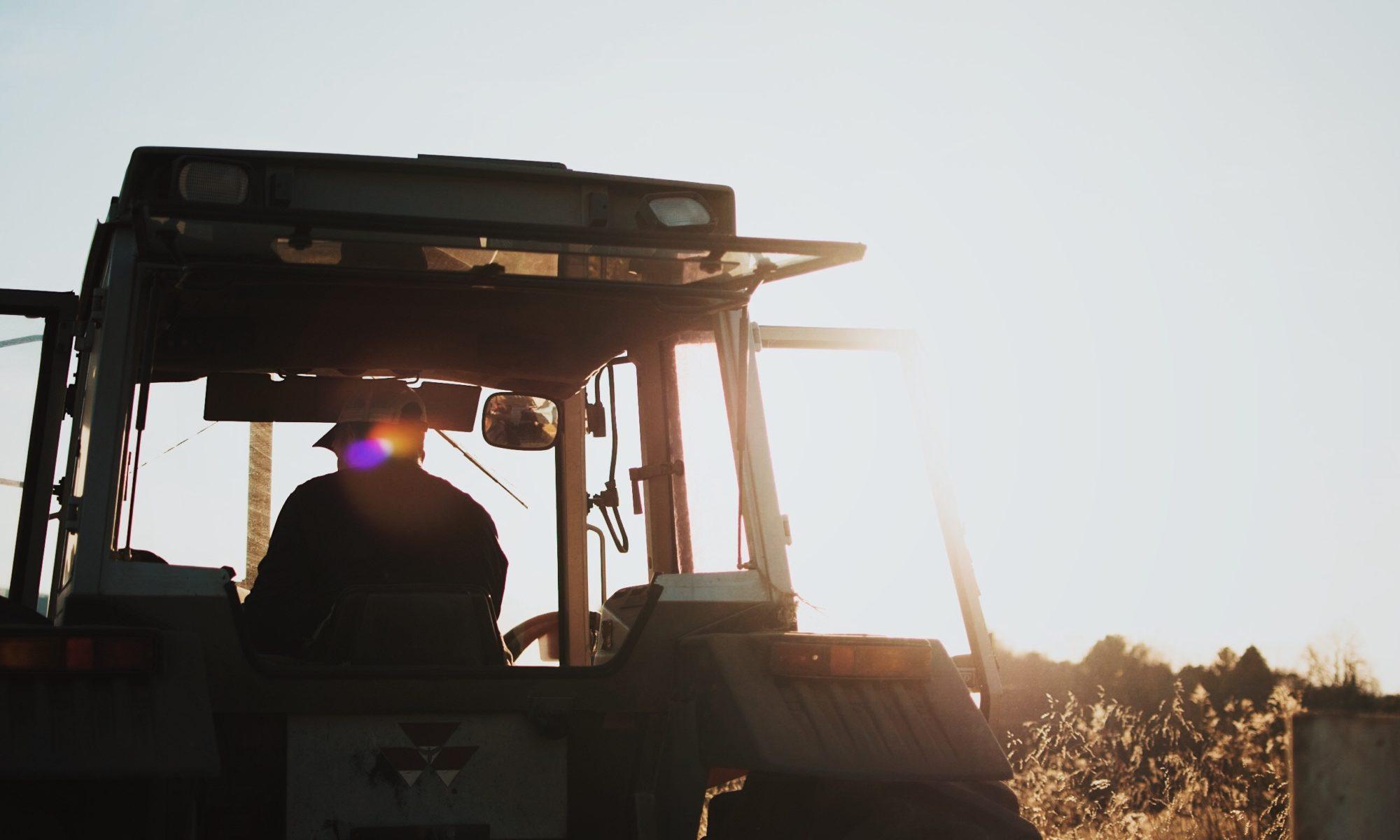 Bauer auf meinem Traktor im Sonnenschein