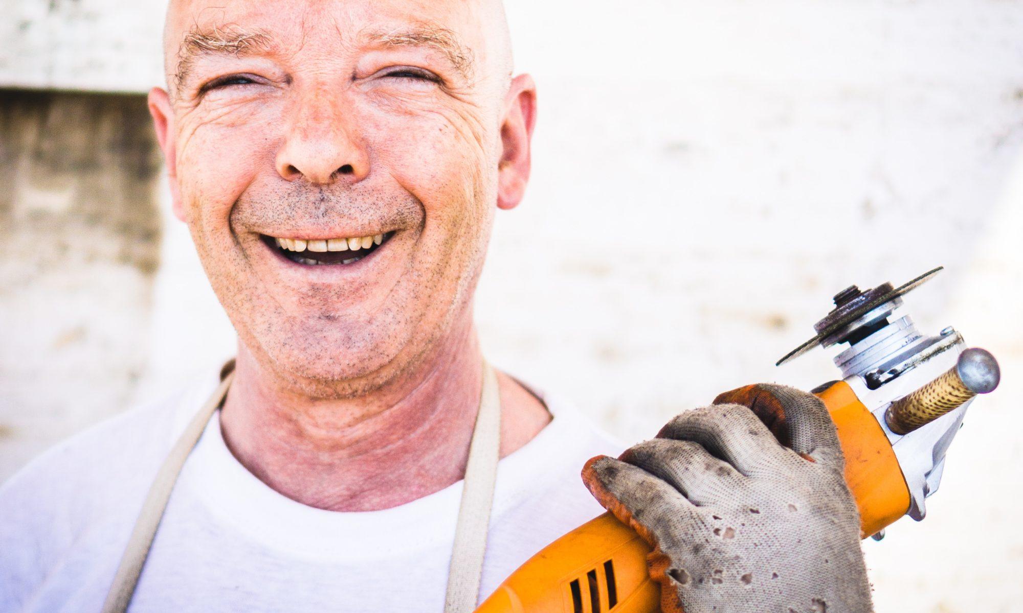 lächelnder älterer Mann mit Werkzeug in der hand